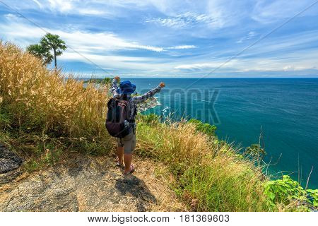 Man with hiking equipment walking at Phromthep cape viewpoint in Phuket Thailand - success concept