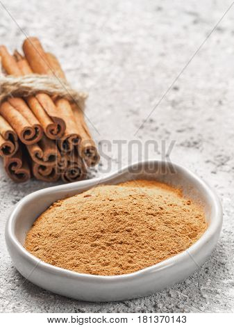 Close up view of ground cinnamon in trendy plate and cinnamon sticks on gray cement background. Vertical. Copy space.