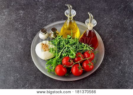 Ingredients for the traditional Italian caprese salad on a glass trey on a grey background with bottles of olive oil and wine vinegar.
