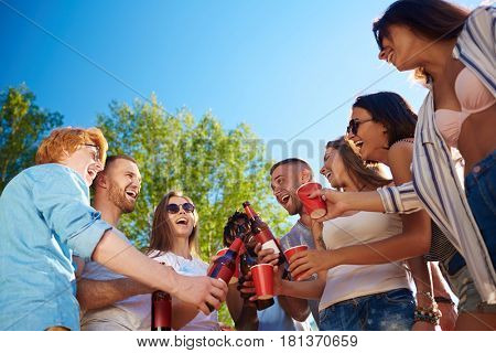 Cheerful buddies toasting with drinks at party