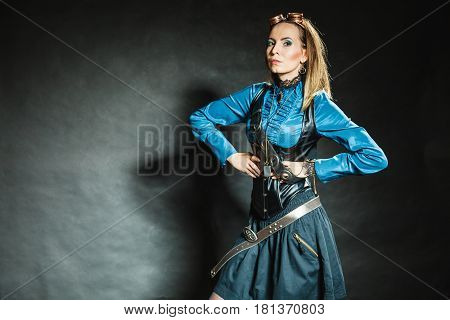 Steampunk and retro style. Attractive vintage woman with stylish accessories on dark background. Fashionable female portrait.