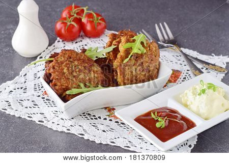 Fried egg plant fritters with tomato and yogurt sauce in a white bowl on a grey abstract background. Healthy food. Healthy breakfast