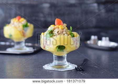 Salad with chicken fillet pineapple mushrooms walnuts in a glass dish on a grey abstract background. Healthy eating concept. Russian traditional food.