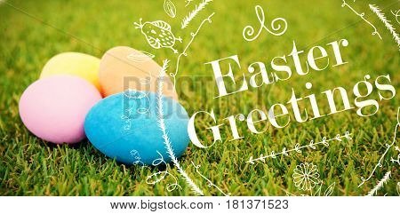 Happy Easter red logo against a white background against painted easter eggs arranged on grass