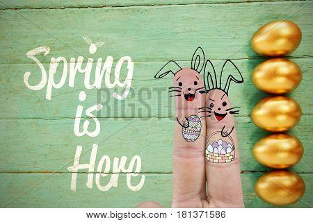 Illustration of fingers representing Easter bunny against golden easter eggs arranged on wooden surface