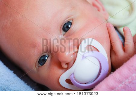Newborn Baby Lying In Bed With Dummy