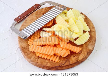 Potato and sweet potato yams peeled and cut in pieces with a special knife with ribs on a cutting board on a grey background. Cooking step by step. Home cooking Healthy eating concept