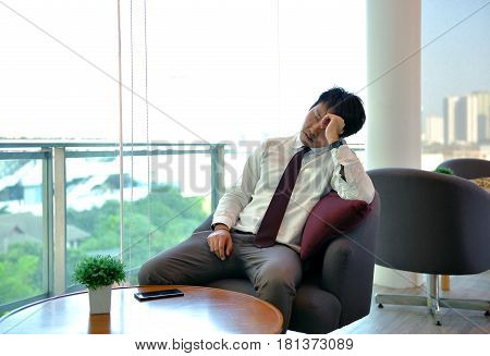 An Asian Business Man Is Tired Between Work, Taking A Nap