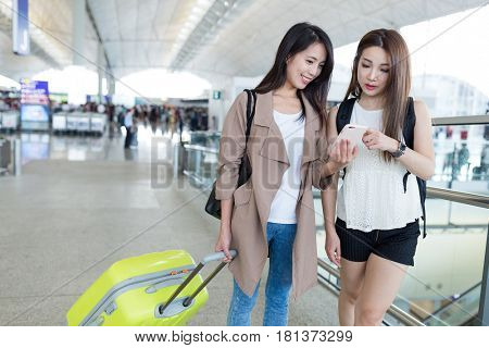 Two girlfriends using cellphone in airport