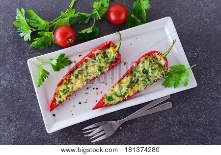 Oven cooked red paprika stuffed with cheese garlic and herbs on a white plate with parcley and cherry tomatoes an abstract grey background. healthy eating concept. Mediterranean lifestyle.