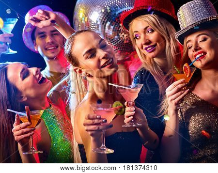 Cocktail party with group people dancing and drink cocktail. Happy women in evening dresses and men have fun in night club and disco ball background.