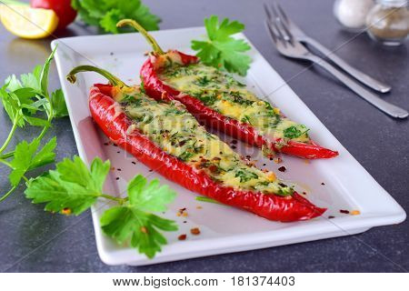Oven cooked red paprika stuffed with cheese garlic and herbs on a white plate with parcley and cherry tomatoes an abstract grey background. healthy eating concept. Mediterranean. Selective focus.