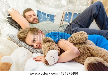 Smiling Father Reading Book To Cute Little Boy Lying And Hugging Teddy Bear