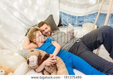 Happy Father And Son With Teddy Bear Reading Book In Blanket Fort