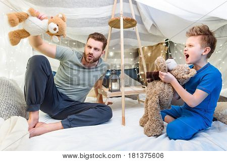Happy Father And Son Sitting In Blanket Fort And Playing With Teddy Bears