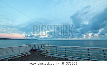 End of San Simeon Public Pier under sunset clouds on the Central Coast of California USA