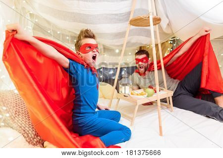 Excited Father And Son In Superhero Costumes Having Fun Together In Blanket Fort