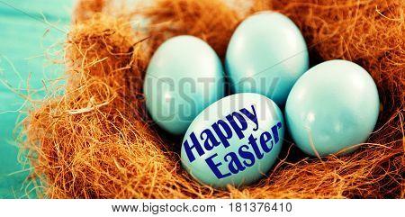 Easter greeting against blue easter eggs in nest