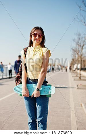 Young Teenage Girl With Small Skateboard, Penny Board, Wear On Yellow T-shirt, Jeans And Sunglasses.