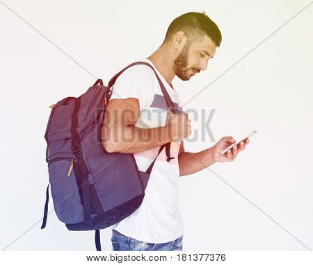 Middle eastern man carrying backpack and using mobile phone