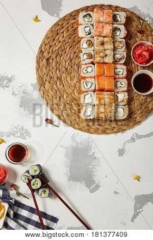 Japanese Sushi - Set of Maki Sushi Roll, Soy Sauce and Ginger over White Texture Background. Top View. Japanese Food Concept