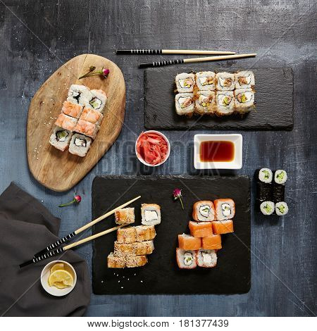 Japanese Sushi - Set of Maki Sushi Roll, Soy Sauce and Ginger over Stone Background. Top View. Japanese Food Concept
