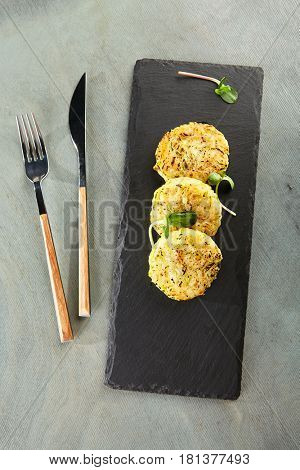 Restaurant Food - Hash Brown Garnish served on Black Slate Dish.  Potato Pancakes Breakfast