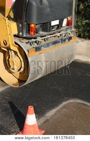 detail of an heavy road roller on the road and a traffic cone