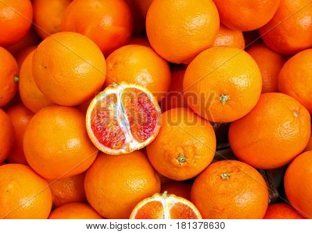 Oranges And An Orange Cut In The Stall Of Greengrocer