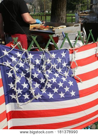 street food stall in the public park with the big American flag and the chef cooking outdoors