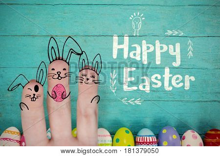 Vector image of fingers painted as Easter bunny against various easter eggs arranged on wooden surface