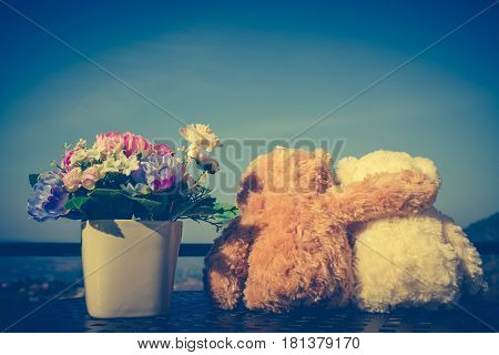 Back view of two doll hugging on table with flowers in vase blue sky background. Concept teddy bears couple with love for valentine day. Greeting or gift card design idea. Vintage effect tone.