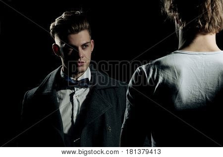 Two handsome men standing opposite on black background. Male model in white tshirt casual wear. businessman in classic bow tie shirt and dark coat. Fashion confrontation.