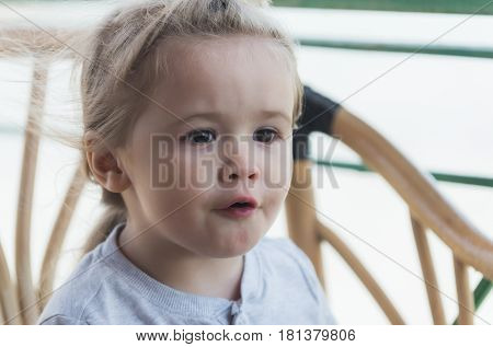 facial emotions. cute baby boy small little caucasian child with brown eyes adorable surprised face and blond hair talking on windy summer day outdoors
