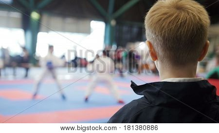 Karate championship - teenager boy looking at karate fighting - spectator at competition, de-focused