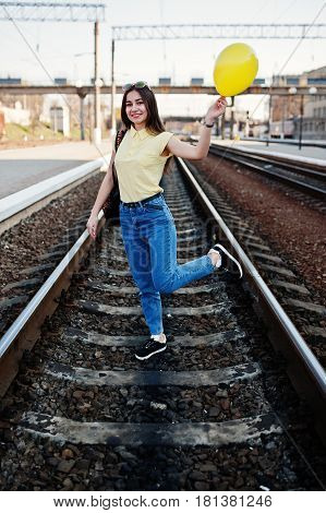 Young Teenage Girl Standing On The Rails At The Train Station With Ballon At Hand, Wear On Yellow T-