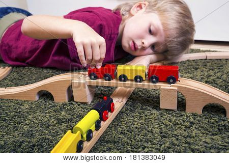 Children play with wooden toy build toy railroad at home or daycare. Toddler boy play with train and cars. Educational toys for preschool and kindergarten child.