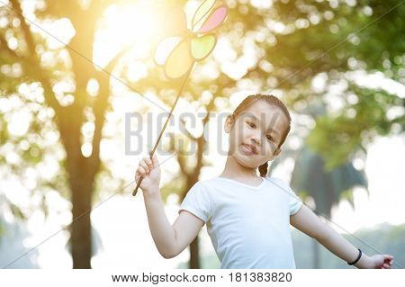 Portrait of cute Asian child playing pinwheel toy outdoors. Little girl having fun at nature park. Morning sun flare background.