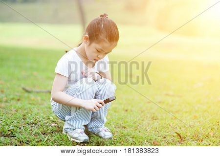 Portrait of Asian school kid with magnifier glass exploring nature at park. Little girl having fun outdoors. Morning sun flare background.