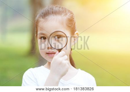 Portrait of Asian kid with magnifier glass exploring nature at park. Little girl having fun outdoors. Morning sun flare background.