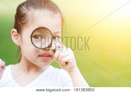 Portrait of cute Asian kid with magnifier glass exploring nature at park. Little girl having fun outdoors. Morning sun flare background.