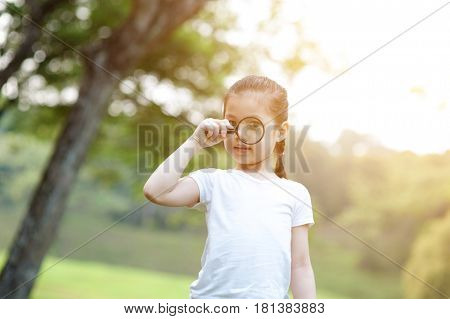 Portrait of Asian girl with magnifier glass exploring nature at park. Little child having fun outdoors. Morning sun flare background.