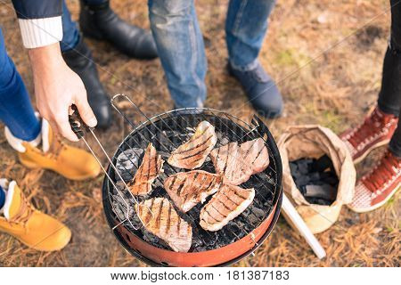 Close-up view of young people grilling meat on a charcoal grill outdoors