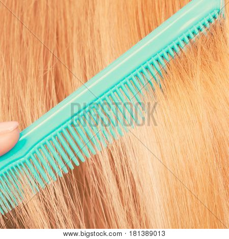 Close Up Of Green Comb In Red Hair.