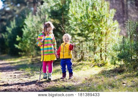 Little boy and girl camping and hiking in sunny summer forest. Kids hike in the Alps mountains. Family with children on autumn trekking trip and camp vacation. Brother and sister play with sticks.