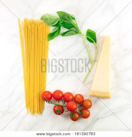 A square photo of basic pasta ingredients on a white marble table. Fresh cherry tomatoes, a slice of cheese, spaghetti, and basil leaves, forming a frame for text