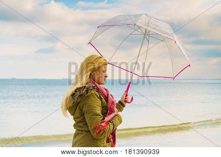 Happiness enjoying cold autumn weather feeling great concept. Woman standing with transparent umbrella on beach near sea sunny day and clear blue sky