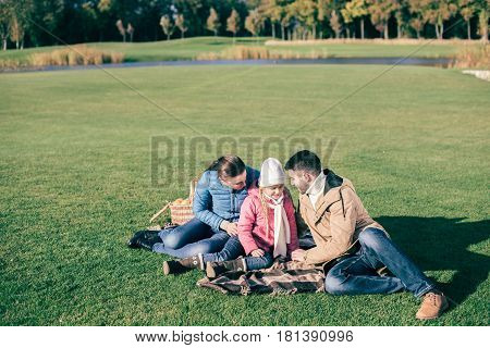 Beautiful Family Sitting On Green Meadow