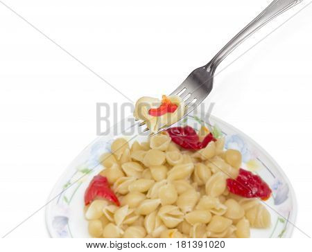 Fragment of the stainless steel fork with some cooked seashell shaped pasta over of a dish with the same pasta on a light background
