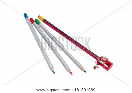 Manual prism pencil sharpener in red plastic housing pencil with long shavings during sharpening and three colored pencils on a light background
